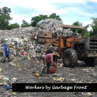 Workers close to machinery near dump front.