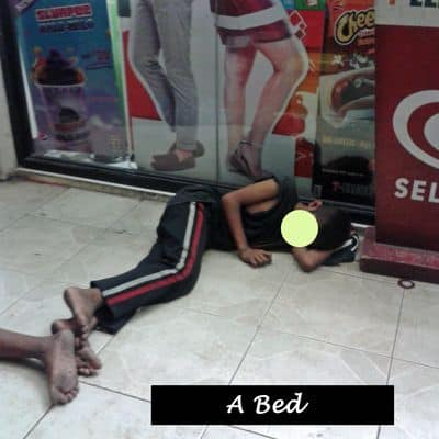 A young boy sleeping in relative safety outside a store.