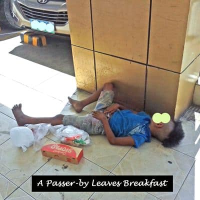 A passerby leaves breakfast for a young boy asleep on the pavement outside a store.