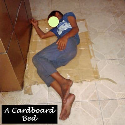 A young boy using cardboard as a bed as he sleeps in relative safety outside a store.
