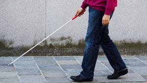 Blind man using walking cane