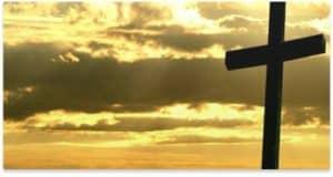 Cross against a yellow skyline.