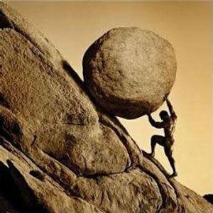 Man rollowing a large boulder up a steep hillside