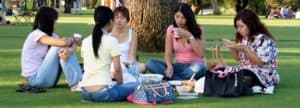 Group of girls sitting in a circle on the grass eating.