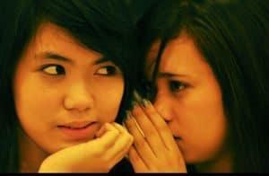 Two girls having a secret conversation