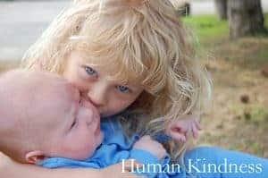 Young girl hugging baby