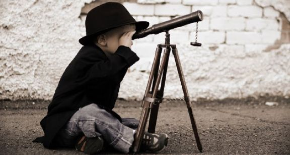 Small boy looking through a telesope