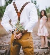 Man facing girl while hiding a bunch of flowers behind his back