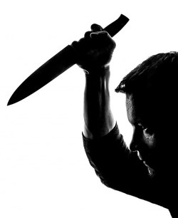 Silhouette of man holding a knife