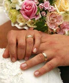 Couple holding hands and displaying their wedding rings