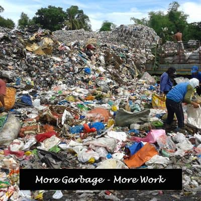 Workers surrounded by rubbish on dump.