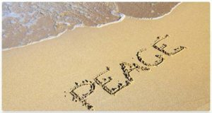 """Word """"Peace"""" etched in sand at waters edge."""