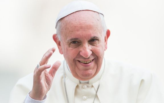 Pope Francis smiling and waving.
