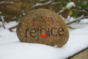 "Stone with the word ""Rejoice"""