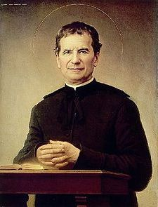 Image of St John Bosco standing behind a table.