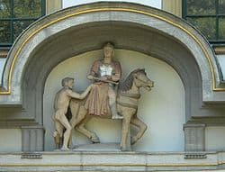 Stone statue of St Martin on horseback sharing his cloak with a poor beggar.
