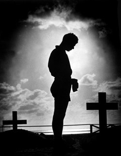 Silhouette of Man standing at a grave.