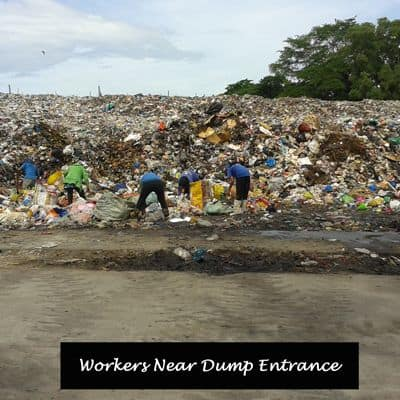 Workers at the front end of a garbage dump.