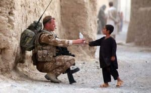 Soldier and young boy sharing a bottle of drink