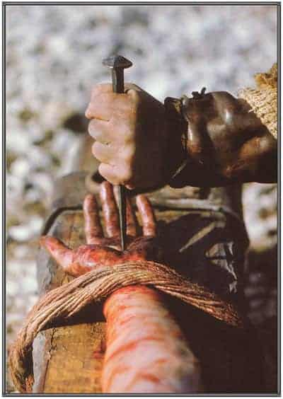 A nail being driven through Jesus' hand