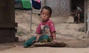 Child in poor community sitting in street